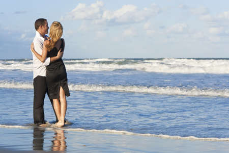 A young man and woman having fun dancing as a romantic couple on a beach with a bright blue sky photo