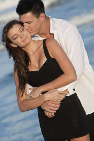 love kissing: A young man and woman embracing and kissing as a romantic couple on a beach  Stock Photo