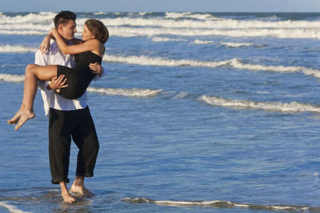 A young man carrying his girlfriend as a romantic couple through the surf on a beautiful beach  photo