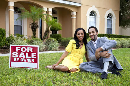 large house: A happy African American man and woman couple outside a large house with a For Sale sign