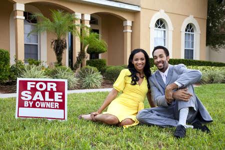 fachada de casa: Una feliz pareja hombre y mujer afroamericana fuera de una casa grande con un signo de For Sale