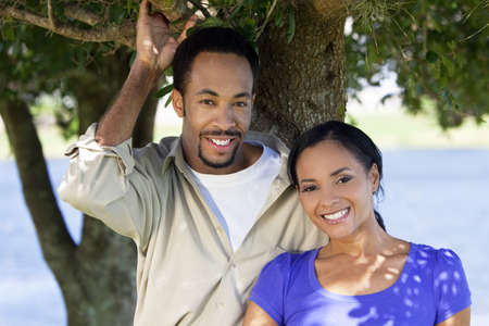 A happy African American man and woman couple standing outside under a tree. Stock Photo - 6217632