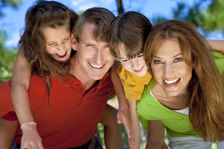 A modern family of father, mother, daughter and son playing together and having doing piggy back in a park Stock Photo - 6229708