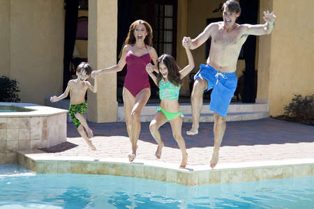 A mother, father and two children family having fun jumping into a swimming pool