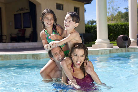 villas: A mother and father having fun on vacation playing with their children on their shoulders in a swimming pool