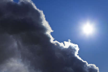 storm cloud: Photograph showing the sun and blue sky emerging from behind a storm cloud. Stock Photo