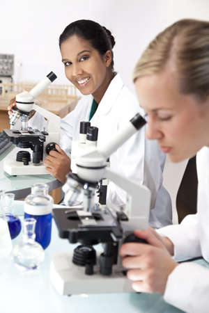 An Asian female medical or scientific researcher or doctor using her microscope in a laboratory with her blond colleague out of focus in the foreground. Stock Photo - 6254890