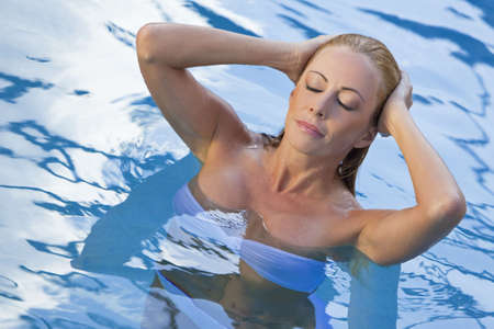 A beautiful and sexy young blond woman wearing a white bikini pushes her hair back as she emerges from a turquoise blue swimming pool. Spa, healthy living and health club concept. photo