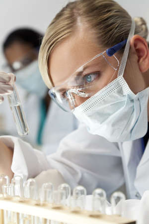 A blond medical or scientific researcher or doctor using looking at a clear solution in a laboratory with her Asian female colleague out of focus behind her. photo
