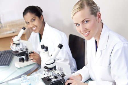 A blond female medical or scientific researcher or doctor using her microscope in a laboratory with her Asian colleague out of focus behind her. Stock Photo - 6305108