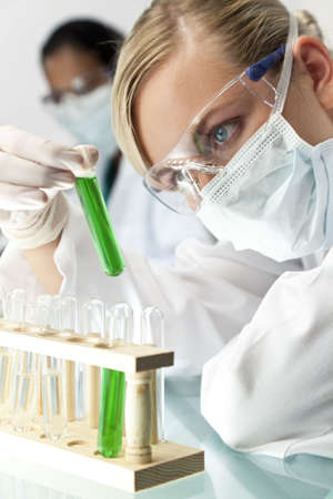 A blond medical or scientific researcher or doctor using looking at a test tube of green solution in a laboratory with her Asian female colleague out of focus behind her. Stock Photo - 6305106