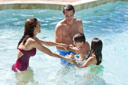 wealthy lifestyle: Una madre e un padre divertirsi in vacanza a giocare con i loro bambini sulle loro spalle in una piscina  Archivio Fotografico