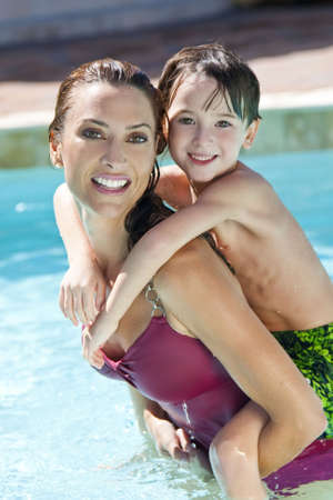 A beautiful mother having fun with her son on her shoulders in a swimming pool photo