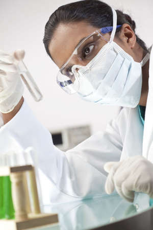 A female Asian medical or scientific researcher or doctor looking at a test tube of clear solution or liquid in a laboratory. photo