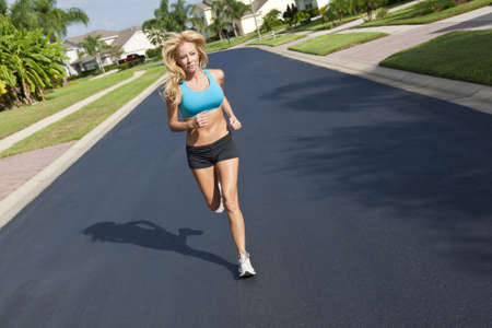 A beautiful fit and healthy blond woman road running down a suburban street in summer sunshine Stock Photo - 6305126