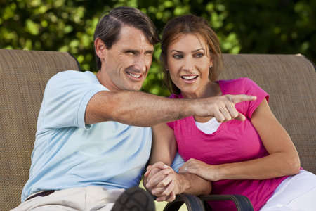 togther: Portrait shot of an attractive, successful and happy middle aged man and woman couple in their thirties, sitting togther holding hands and smiling while the man is pointing off camera.