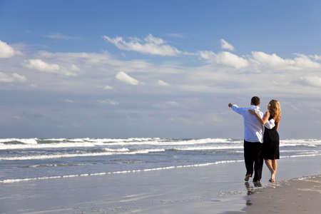 A young man and woman couple having a romantic walk on a beach with a bright blue sky photo
