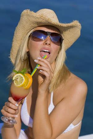 cappello cowboy: Bellissima giovane donna bionda in paglia cappello da cowboy e occhiali da sole godendo un cocktail da un mare blu profondo Archivio Fotografico