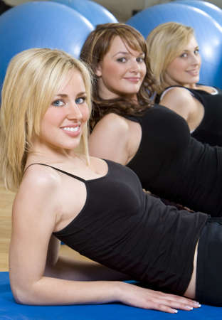 Three beautiful young women, two blond, one brunette, working out on on mats doing aerobic sit ups at the gym. The focus is on the blond girl with blue eyes in the foreground. photo