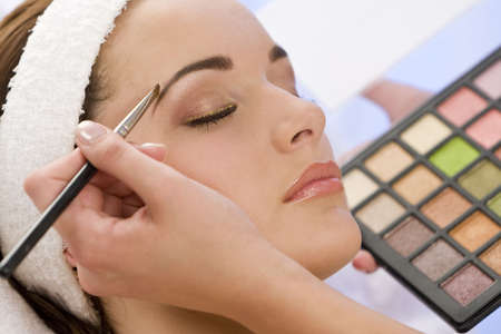 beautician: A beautiful young woman having her make up applied by a beautician in health spa. Stock Photo