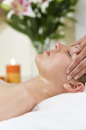 A young woman relaxing at a health spa while having a relaxing destressing head massage Stock Photo - 6336219