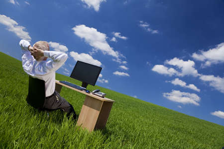 blue sky thinking: Business concept shot of a middle aged man or businessman relaxing with hands behind his head at an office desk with computer in a green field with a bright blue sky. Shot on location.