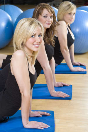 Three beautiful young women, two blond, one brunette, working out on on mats doing aerobic stretching at the gym. The focus is on the blond girl with blue eyes in the foreground. photo