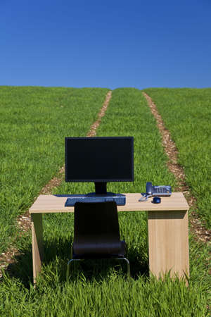 Business concept shot showing a computer on a desk in a green field with a blue sky and a path leading over the horizon. Shot on location not in a studio. photo