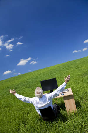 silver surfer: Business concept shot showing an older male executive arms raised using a computer in a green field with a blue sky complete with fluffy white clouds. Shot on location not in a studio.