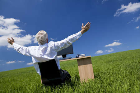 Business concept shot showing an older male executive arms raised using a computer in a green field with a blue sky complete with fluffy white clouds. Shot on location not in a studio. photo
