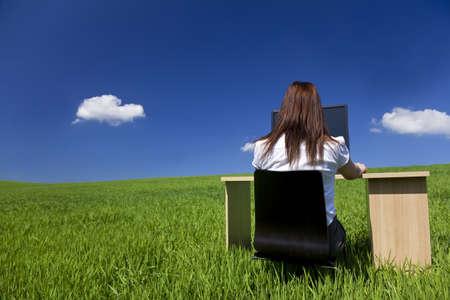 Business concept plan d'une jeune femme travaillant à un bureau et l'ordinateur dans un champ vert avec un ciel bleu et les nuages ??blancs pelucheux. Filmé sur place.