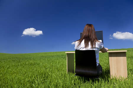 blue sky thinking: Business concept shot of a young woman working at an office desk and computer in a green field with a bright blue sky and fluffy white clouds. Shot on location. Stock Photo