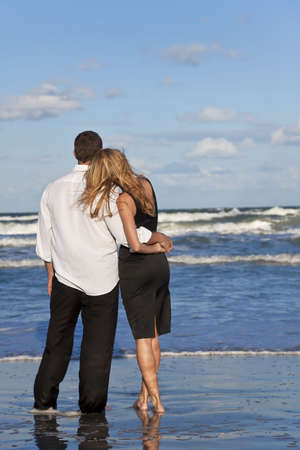 couple cuddling: A young man and woman embracing as a romantic couple on a beach with a bright blue sky