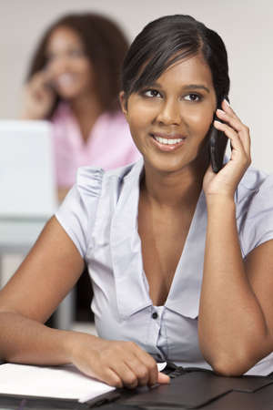 A beautiful young Indian Asian business woman with a wonderful smile in an office talking on her cell phone with her female colleague out of focus behind her. photo