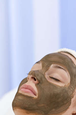 A beautiful young woman relaxing and having a chocolate face mask facial at a health spa photo