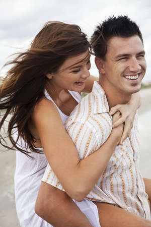 couple cuddling: A young man and woman romantic couple having fun playing piggy back on a beach and laughing together. Stock Photo