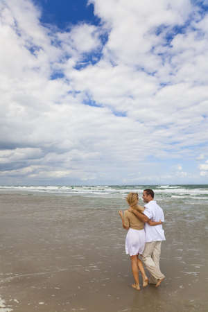 A young man and woman couple having romantic walk on a beach Stock Photo - 6384992