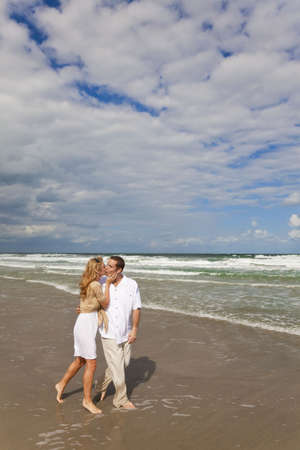 A young man and woman walking and kissing as a romantic couple on a beach photo