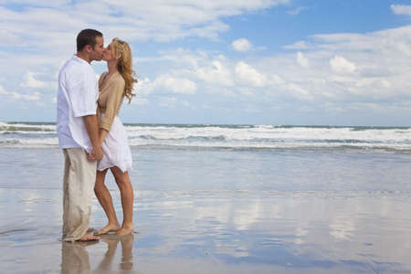 honeymoon couple: A young man and woman holding hands and kissing as a romantic couple on a beach