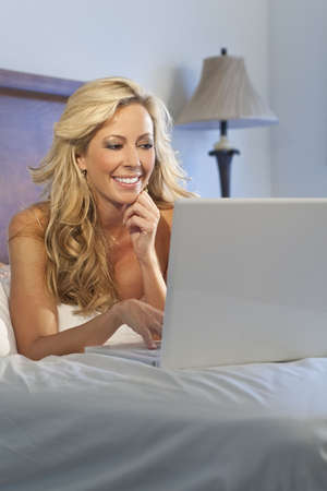 A beautiful happy and smiling young blond woman using her white laptop to surf the internet in bed photo