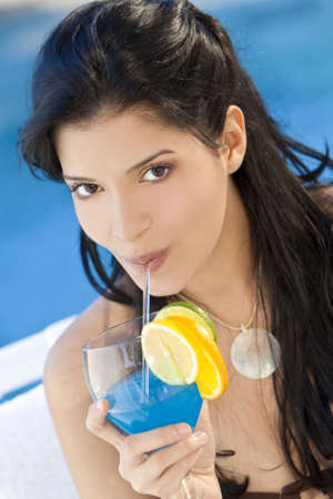 Stunningly beautiful young latina Hispanic woman in drinking a cocktail by a blue swimming pool photo
