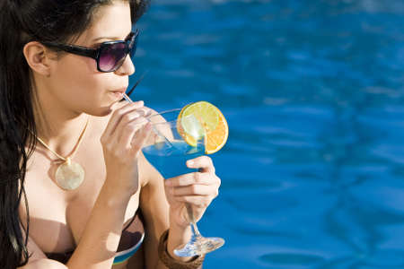 Stunningly beautiful young latina Hispanic woman drinking a cocktail by a blue swimming pool photo