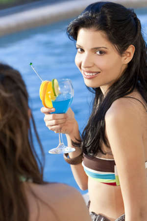 Stunningly beautiful young latina Hispanic woman in drinking a cocktail by a blue swimming pool with her friend in the foreground. photo