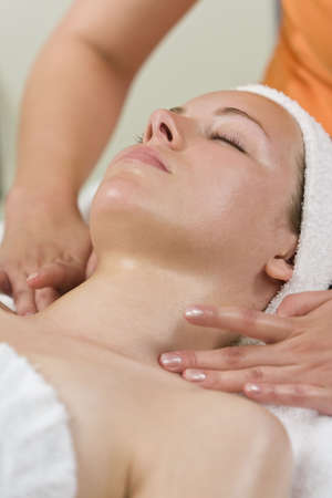A young woman relaxing at a health spa while having a facial treatment or relaxing massage Stock Photo - 6384974