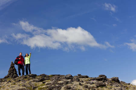 A young couple hiking in stony mountains standing next to a stone pile tor or signpost pointing to the distance. Shot on location in Iceland. photo