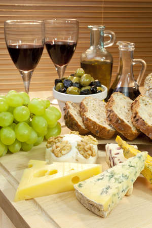 beverage display: A platter of Mediterranean food including cheese, grapes, wine, bread, olives, olive oil and balsamic vinegar. Shot in beautiful warm light with the focus on the cheese in the foreground.