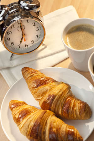 A continental breakfast of croissant pastries and coffee Illuminated with golden early morning sunshine and accompanied by a classic alarm clock set at 7am