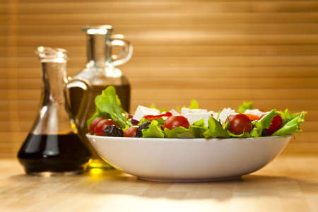 Tomato, mozzarella, or feta cheese salad with black olives, olive oil and balsamic vinegar dressing in bottles out of focus in the background, shot in golden sunshine