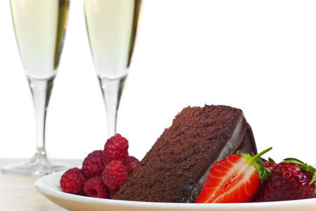 champagne flute: A plate of chocolate cake, raspberries and sliced strawberries with two flute glasses of champagne in the background.