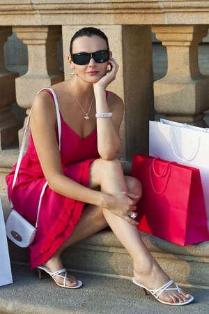 full red: Una classica bella donna Latina Hispanic Mediterraneo seduta e il pensiero circondato da borse della spesa pieno rossi e bianchi Archivio Fotografico